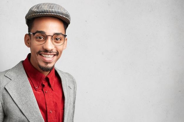 Felice studente maschio nerd o wonk indossa giacca e berretto alla moda, arriva per superare l'esame