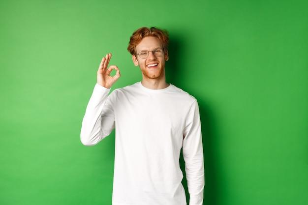 赤い髪の幸せな男子生徒、眼鏡をかけて、承認の大丈夫なサインを示し、満足のいく笑顔を示し、緑の背景の上に立っています。