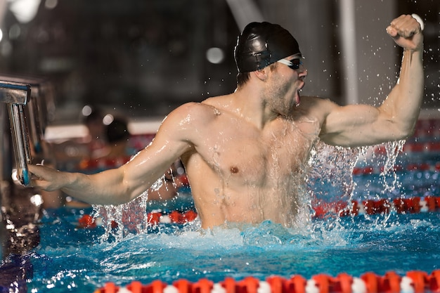 Happy male swimmer holding starting block