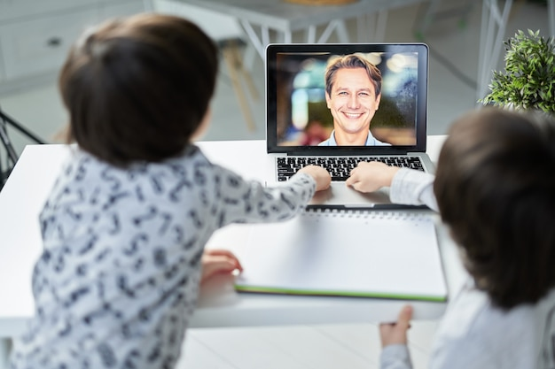 子供のためのオンラインレッスン中に彼の小さな生徒に微笑んで幸せな男性教師。テーブルに座ってラップトップを使用している2人のヒスパニック系の男の子。子供のための遠隔教育。ノートパソコンの画面に焦点を当てる