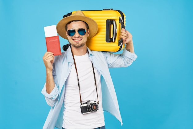パスポートとビザのチケットを手に黄色のスーツケースを持つ幸せな男性観光客。高品質の写真