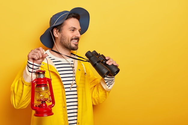 Happy male traveler has outdoor activities, explores world, uses binoculars and torch dressed in waterproof raincoat leads active lifestyle isolated on yellow