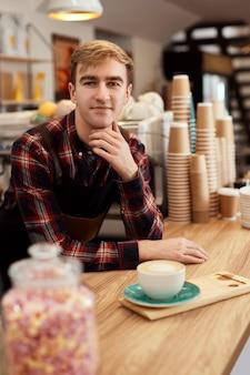 커피숍에서 뜨거운 음료를 마시며 앞치마를 입은 행복한 남성 웨이터, 바리스타는 카페테리아에서 일하게 되어 기쁩니다