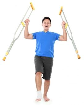 목발을 사용하여 부러진 발로 행복한 남성