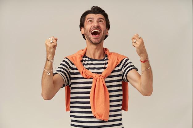 검은 머리카락과 강모가있는 행복한 남성. 줄무늬 티셔츠를 입고 어깨에 스웨터를 묶었습니다. 팔찌, 반지가 있습니다. 주먹을 쥐고 승리를 축하하세요