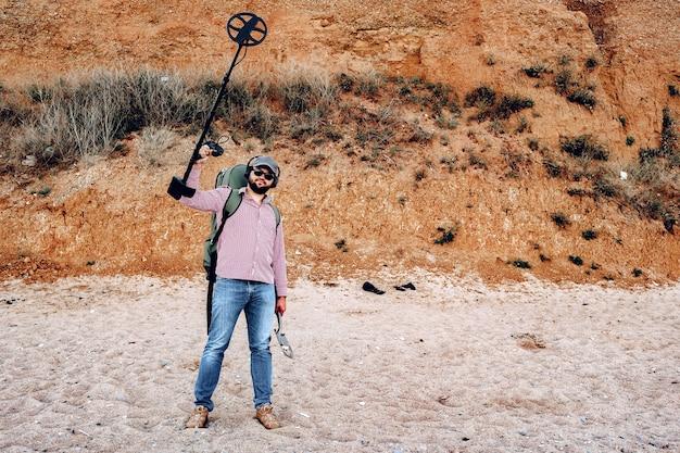 金属探知機を持つ幸せな男性がビーチで何かを見つけました