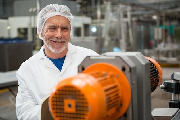 Счастливый рабочий-мужчина, стоящий у машин на заводе холодных напитков