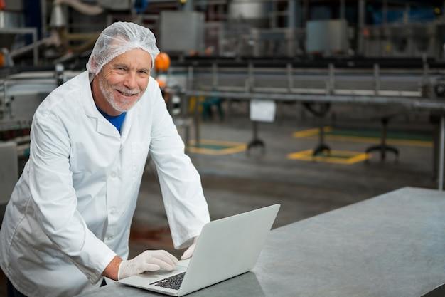 Счастливый работник мужского пола, использующий ноутбук на заводе