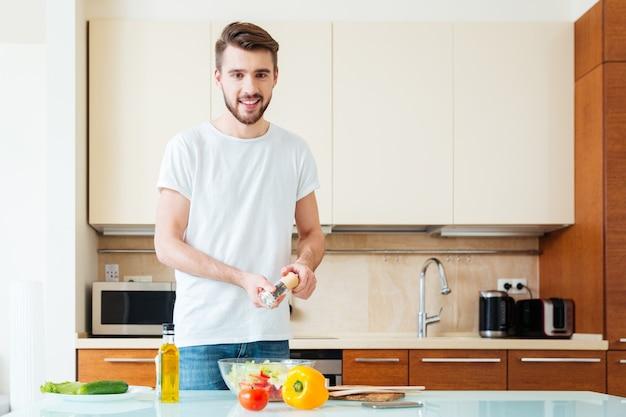 キッチンでサラダにスパイスを追加し、正面を見て幸せな男
