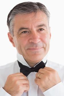Happy man adjusting his bow tie