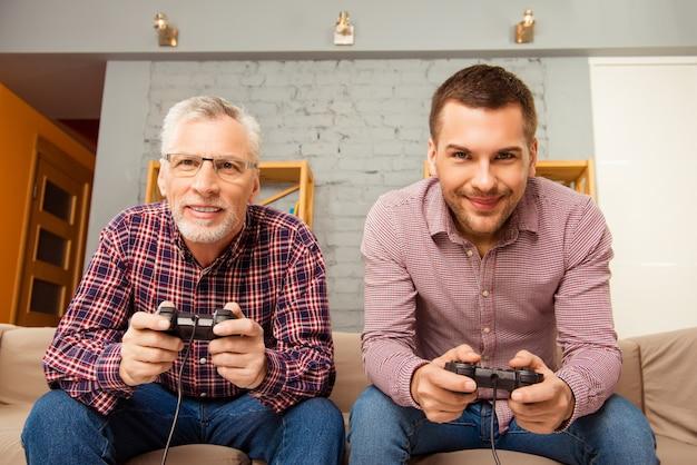 Счастливый человек и его отец играют в видеоигры, сидя на диване