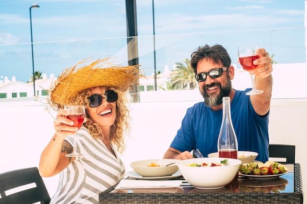 幸せな男性と女性の大人の成熟したランチと赤ワインをお楽しみください