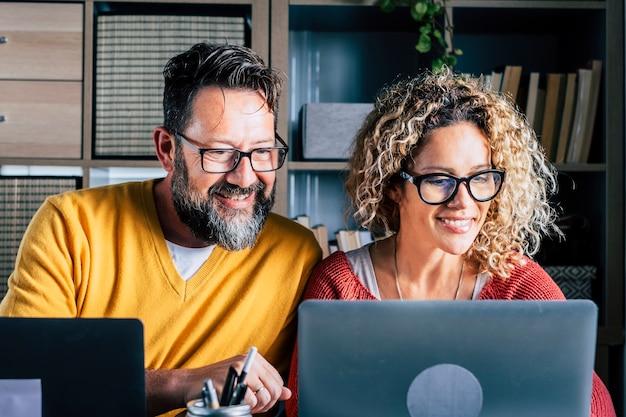 幸せな男性と女性のカップルは、喜びと一緒にスマートなオフィス活動で自宅で働いています-オンラインインターネットの仕事活動でデジタル現代の大人の人々-コンピュータを使用して陽気な女性と男性