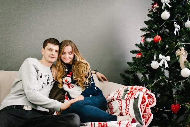 インテリアの家のクリスマスツリーの近くにサンタクロースのセーターを着た幸せな男と女。夜のクリスマス。家族での休暇を楽しんでいます。メリークリスマス、そしてハッピーニューイヤー。