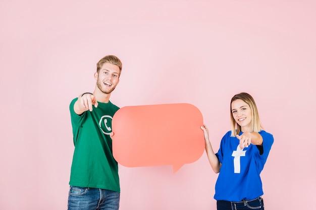 Счастливый мужчина и женщина gesturing при проведении пустой оранжевый пузырь речи
