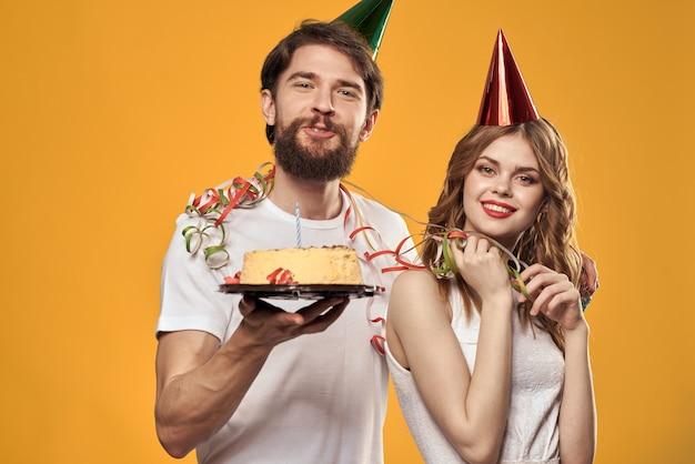 手にケーキと黄色の背景で誕生日を祝う帽子の幸せな男と女。高品質の写真