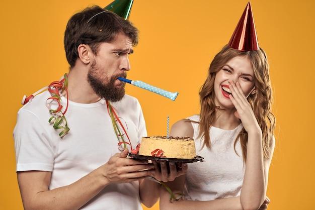 ケーキを手に黄色い空間で誕生日を祝う帽子をかぶった幸せな男女。