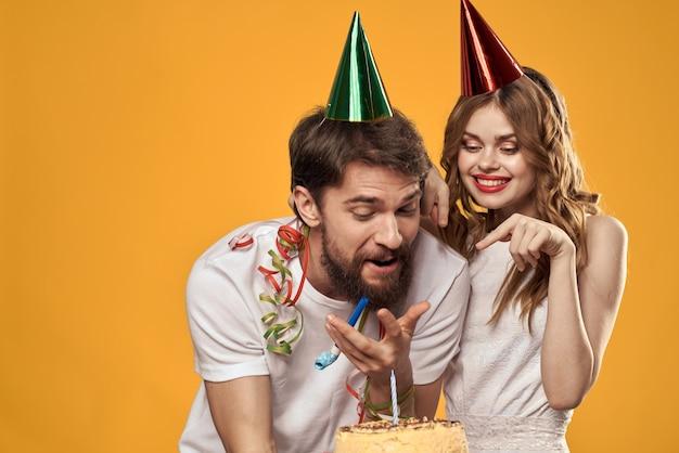 黄色の誕生日を祝う帽子の幸せな男と女