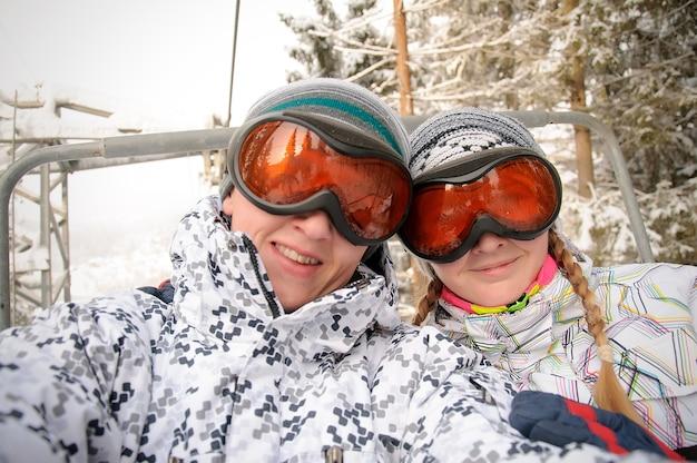 カルパティア山脈のリフトでスキー眼鏡の幸せな男と女が上昇します。閉じる。冬の自然。