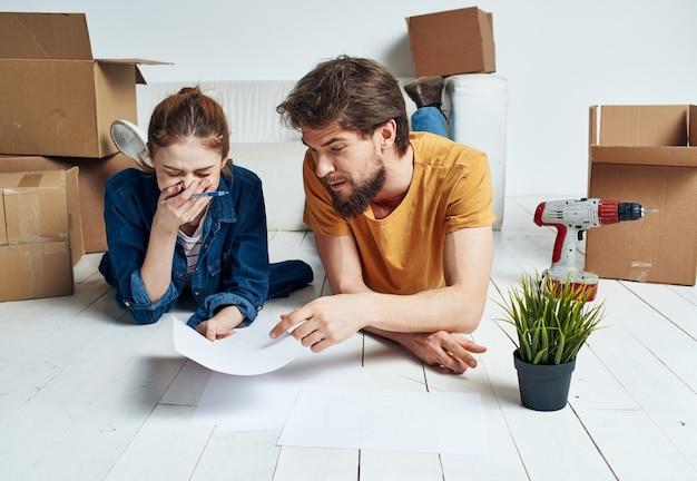 Счастливые мужчина и женщина лежат на полу цветок в горшке, планируя будущие ремонтные работы