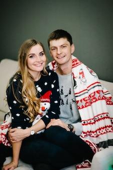 インテリアホームナイトクリスマスのクリスマスツリーの近くで幸せな男と女。