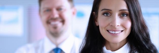Счастливый мужчина и женщина офисные работники, улыбаясь на работе. содействие в разработке инвестиционных проектов. бизнес-план разрабатывает стратегию развития предприятия. спокойные бизнесмены во время глобальной пандемии