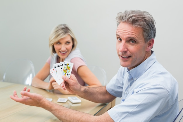 Счастливый мужчина и женщина, играющие в карты дома