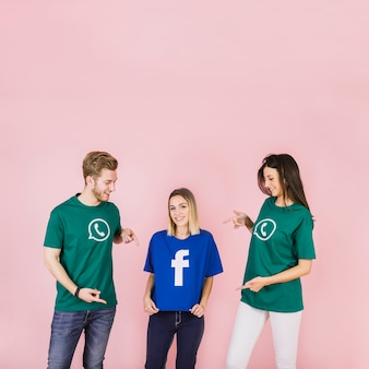 Happy man and woman pointing at her friend using facebook t-shirt