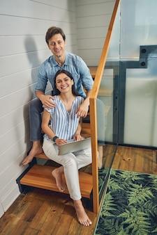 행복 한 남자와 여자는 그녀의 다리에 노트북을 들고 여성 동안 나무 계단에 앉아