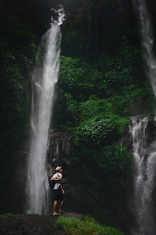 Happy man backpacker enjoying amazing tropical waterfall on  nature landscape. travel lifestyle and success concept vacations into the wild nature on mountain and rainforest