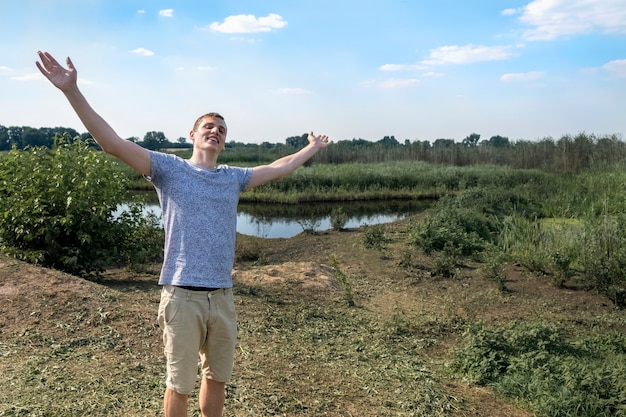 Happy man breathing deeply fresh air standing against lake and field a sunny day
