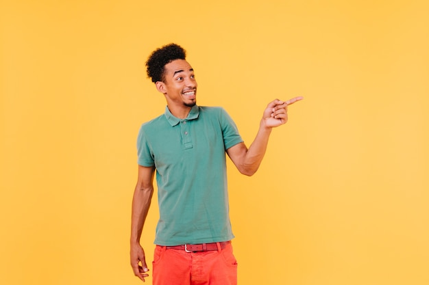 Happy man in bright outfit pointing finger to something. portrait of handsome african male model.
