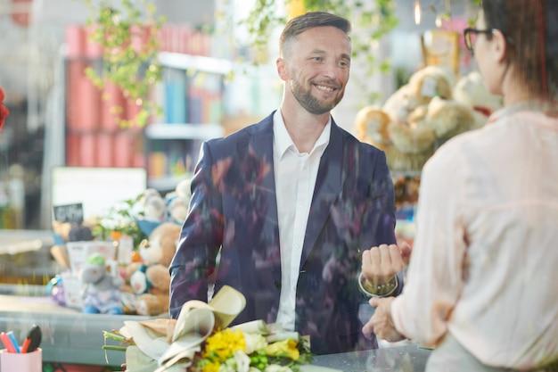 Happy man buying flowers