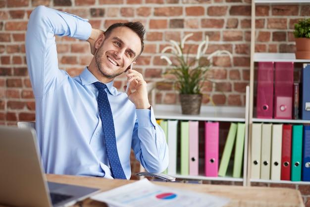 幸せな男がオフィスに電話