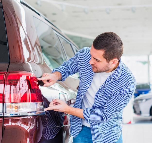 Happy man in car dealership