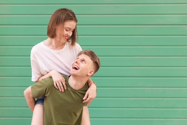 幸せな男は彼のガールフレンドを背負って、彼女を見て、笑っています。