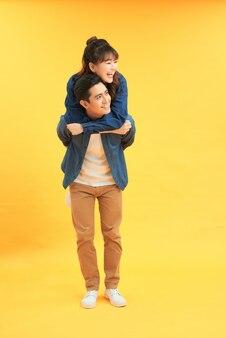 Счастливый человек, несущий свою подругу на спине на желтом фоне