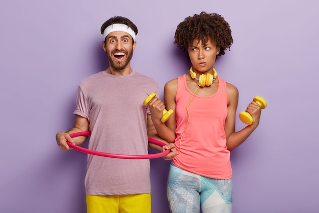 Uomo felice in abbigliamento casual, altalene hula hoop, donna dalla pelle scura alza le braccia con manubri, vestito con abbigliamento sportivo, fa diversi esercizi fisici, isolato sopra il muro viola. sport e allenamento