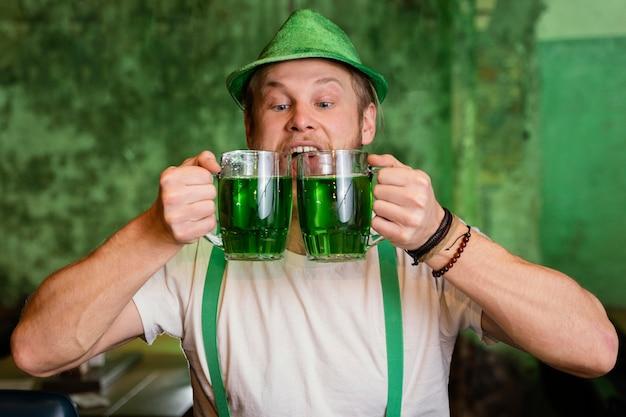 Uomo felice che celebra st. patrick's day al bar con bevande