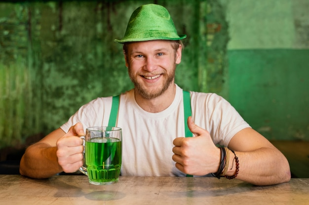 Happy man celebrating st. patrick's day with drink