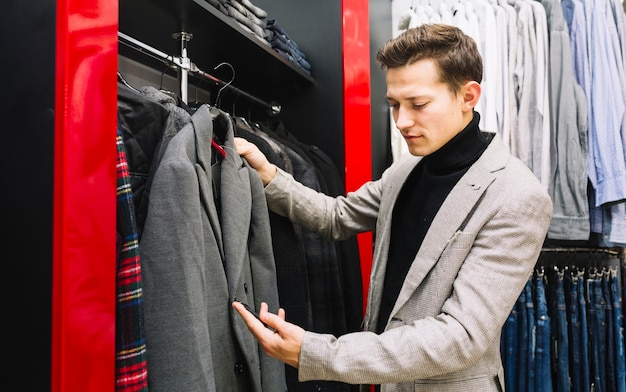 Happy man checking price tag of coat in store