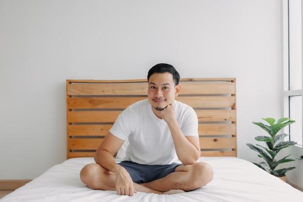 健康な心の彼のベッドの概念で身も凍るようにリラックスした幸せな男