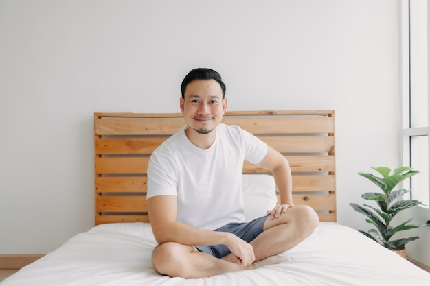 Счастливый человек отдыхает и расслабляется на своей кровати, концепция здорового духа
