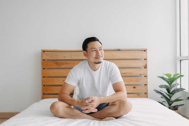 Happy man chilling and relaxed on his bed concept of a healthy mind