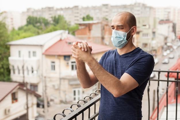 コロナウイルスと戦う医師を支援するためにバルコニーで拍手する幸せな男。