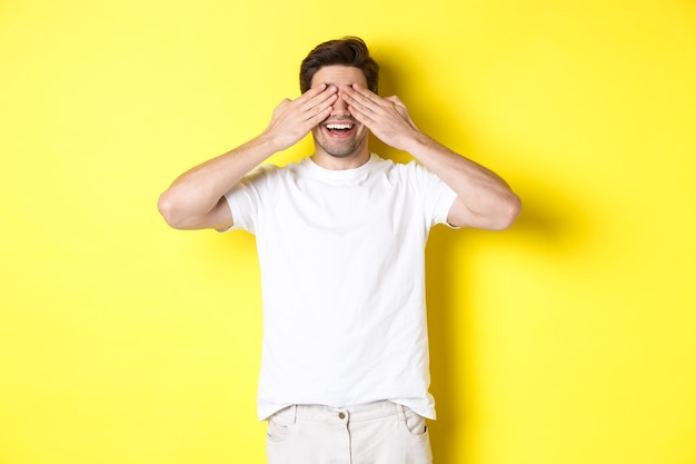 幸せな男は目を閉じて驚きを待って、面白がって笑って、黄色の背景の上に立っています。