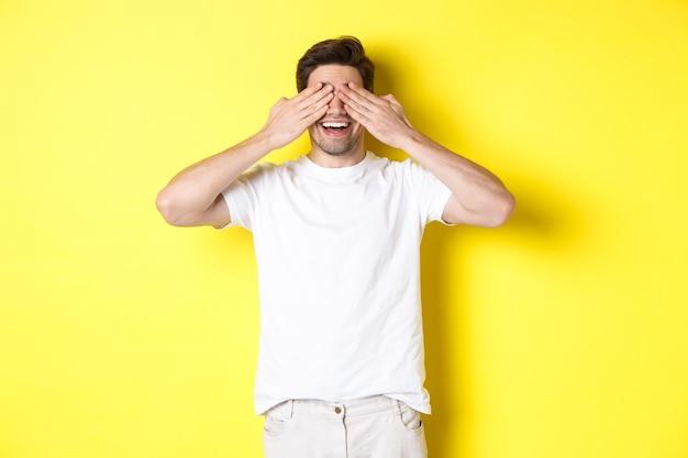 幸せな男は目を閉じて驚きを待って、面白がって笑って、黄色の背景の上に立っています