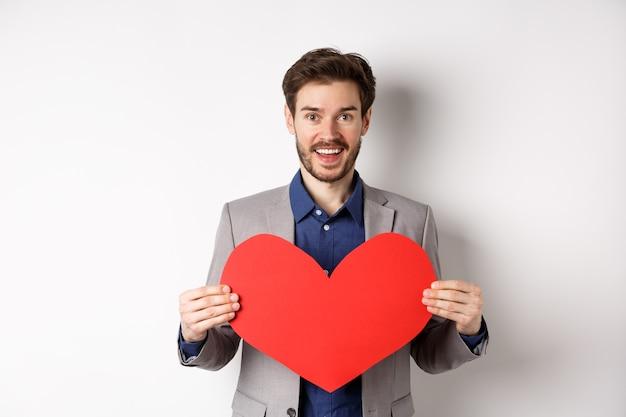 사랑에 고백하고, 심장 컷 아웃을 표시하고 카메라에 웃고, 연인, 흰색 배경으로 낭만적 인 데이트에 맞게 서 행복 한 사람.