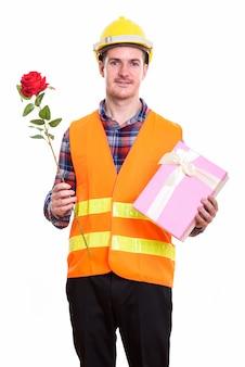 赤いバラを押しながら笑って幸せな男の建設労働者と