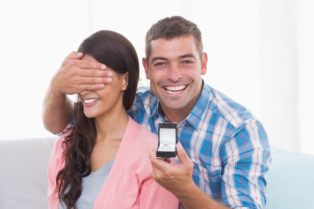 반지를 선물하는 동안 여자의 눈을 덮고 행복한 사람